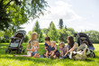 Mothers And Children Enjoying Picnic In Park