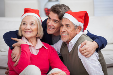 Loving Son With Parents Wearing Santa Hats