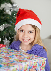 Smiling Girl In Santa Hat Holding Christmas Gift