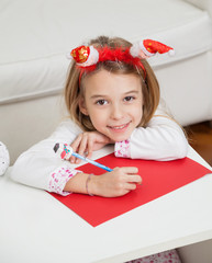 Smiling Girl Making Christmas Greeting Card