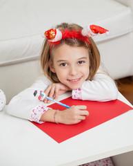 Smiling Girl Making Christmas Greeting Card