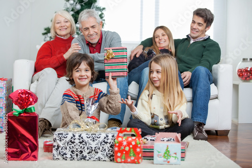 Boy Holding Christmas Gift With Family In House