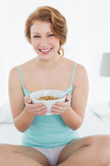 Smiling female with a bowl of cereal sitting on bed