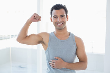 Portrait of a fit man flexing muscles in fitness studio