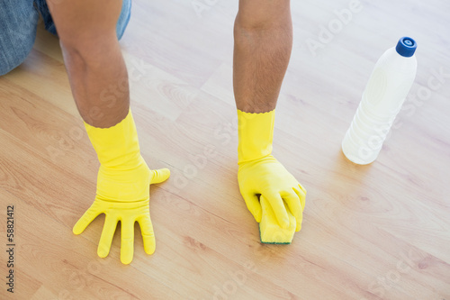 Yellow gloved hands with sponge cleaning the floor
