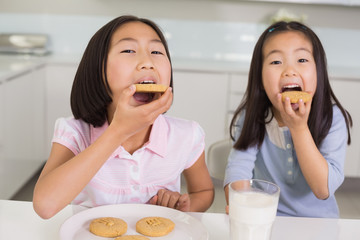 Girls enjoying cookies and milk in kitchen