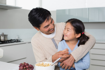 Cheerful father with daughter having cereals in kitchen