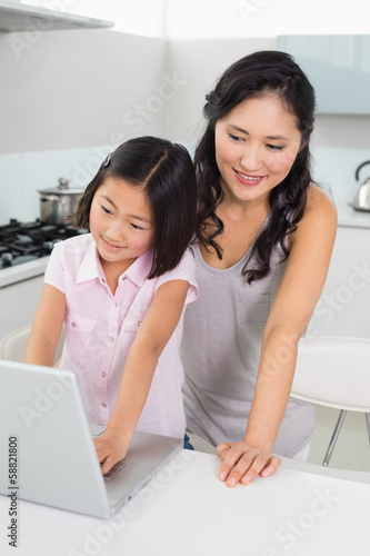 Smiling mother with young daughter using laptop in kitchen