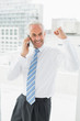 Cheerful businessman using mobile phone in office