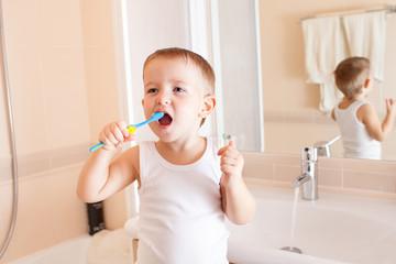 Boy cleaning teeth in bathroom