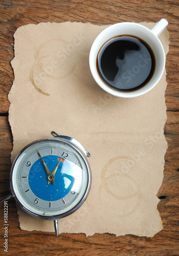 Cup of coffee and clock on sheet of paper with coffee stains