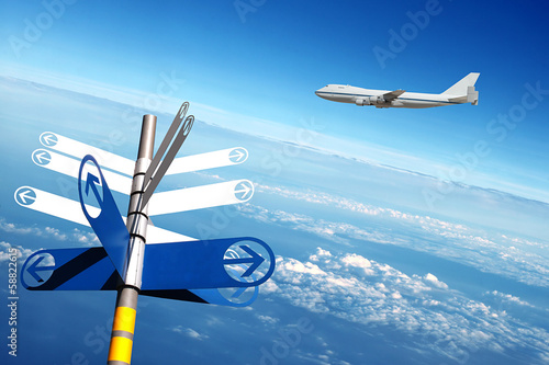 Airplane with signpost in clouds background.