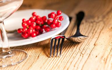 piatto e posate con bacche rosse