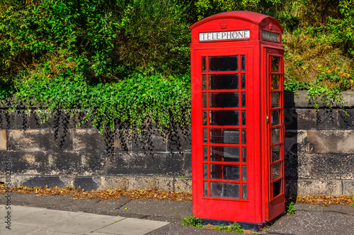 Typical red English telephone booth in the park