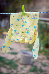 baby clothes and accessories hanging on clothesline outdoors