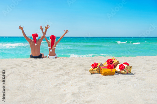 happy couple in santa hats hands up at sea beach with christmas