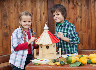 Kids painting the bird house - preparing for winter