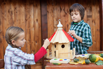 Kids painting the bird house for the winter