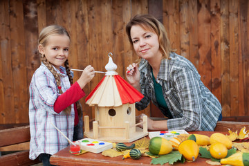 Woman and little girl painting a bird house