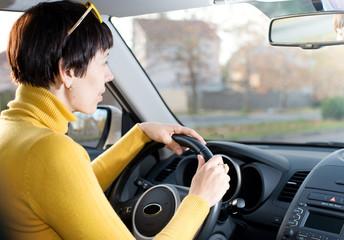 Happy woman sitting in car