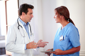 Handsome hispanic doctor talking with lady nurse