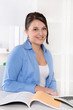 Lachende junge Frau sitzend im Büro - Bluse blau