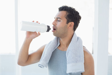 Man with towel around neck drinking water in fitness studio