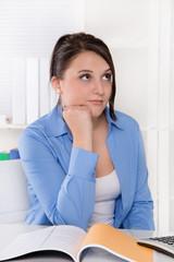Frau nachdenklich und unsicher sitzend im Büro