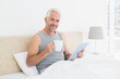 Mature man with digital tablet and coffee table in bed