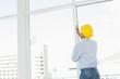 Handyman in yellow hard hat examining window in office