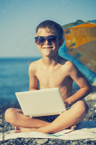 happy smiling kid with laptop on a beach