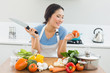 Smiling woman chopping vegetables in kitchen