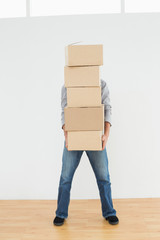 Obscured man carrying boxes in house