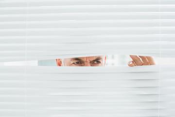 Serious mature businessman peeking through blinds