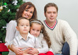 Happy family members sitting over christmas tree