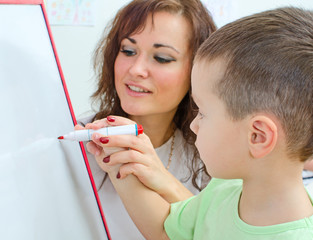 Little boy with teacher near whiteboard