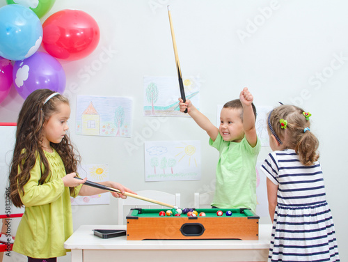 Children playing mini billiard at playroom