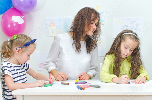 Teacher with two girls in kindergarten.