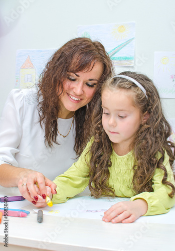 Teacher helps little girl to draw