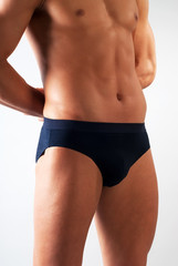 attractive male body fragment with blue underwear on white