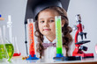 Curious little girl posing with microscope in lab
