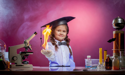 Cute little magician holding fire in palm of hand