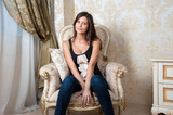 Young pregnant woman sits on chair at home