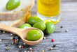 Green olives in a wooden spoon with oil and color peppers