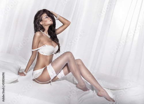Brunette woman posing in bedroom