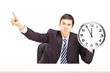 Angry businessman holding a clock and gesturing with his finger