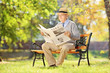 Senior man sitting on a bench and reading a newspaper in autumn