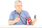 Senior man measuring blood pressure with sphygmomanometer
