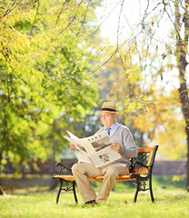 Senior gentleman with hat on bench and reading a newspaper