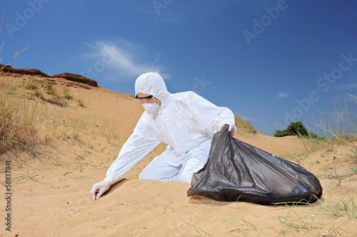 Worker in protective suit holding a waste bag and collecting